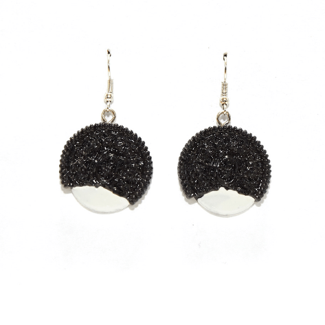 Two earrings with the shape of black cookies with white filling