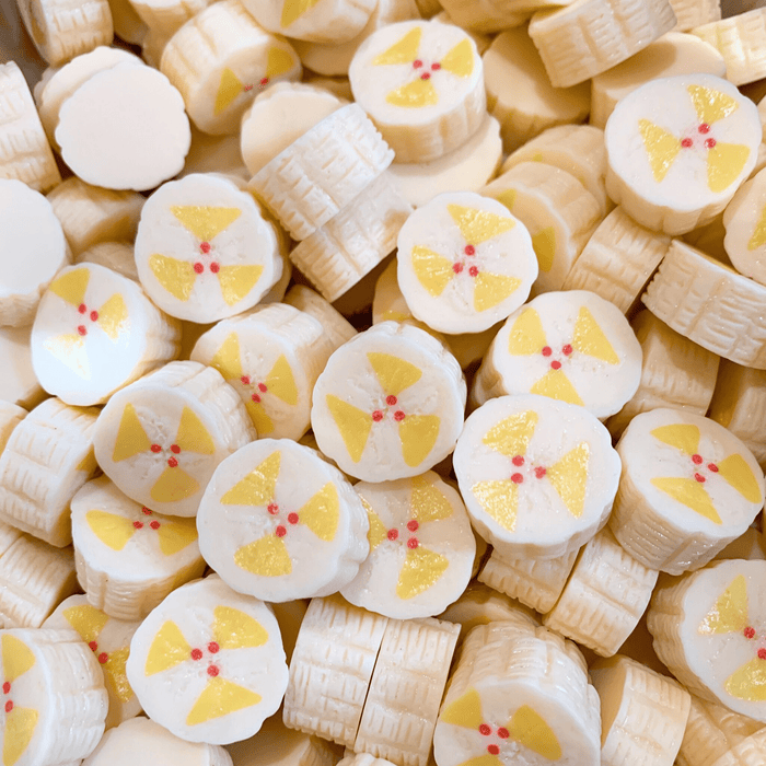 A mix of pale yellow banana slices charms