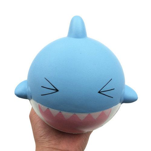 A hand holding a blue round shark quishy with a happy face and open mouth.