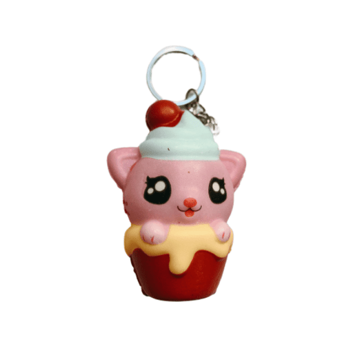 A squishy keychain with the shape of a pink cat, inside a red container with peach drips and light blue icing on its head with a red top