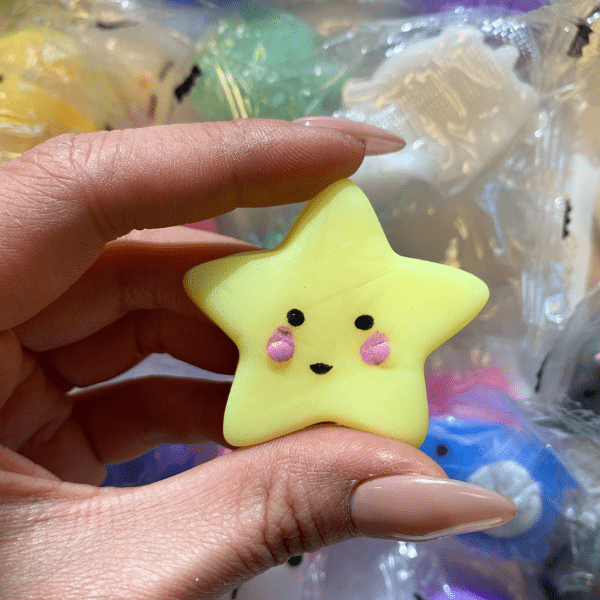 A hand holding a small pale yellow star mochi squishy with pink cheeks and black face and mouth.