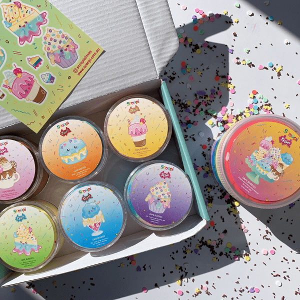 A box containing the Cafe Buddies collection of six slimes and a sticker sheet and the Deluxe Cafe Buddies slime on the outside.