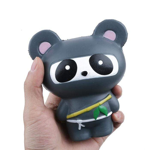 A hand holding a black panda squishy dressed as a panda with a white cord and a bamboo stick.