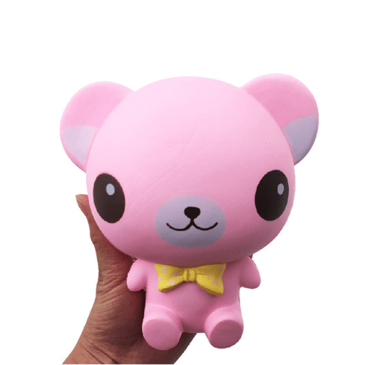 A hand holding a pink bear squishy. It has a big and round head and a small yellow bow tie
