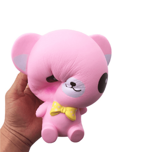 A hand holding a pink bear squishy that has been squished in the face.