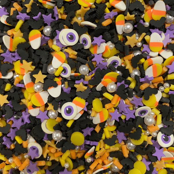 A mix of purple stars, purple and white eyes, corn candy, white round beads and black bat sprinkles.