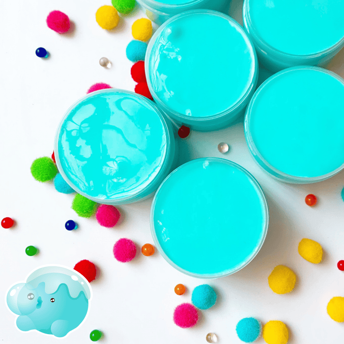 Several blue glossy slimes in their containers viewed from the top with multicoloured pompons in the background.