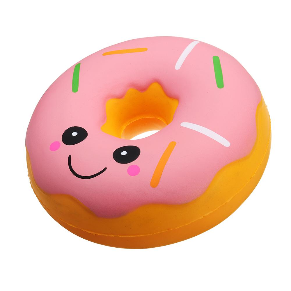 A round donut squishy with pink glazing, round eyes and a smile and multicoloured sprinkles