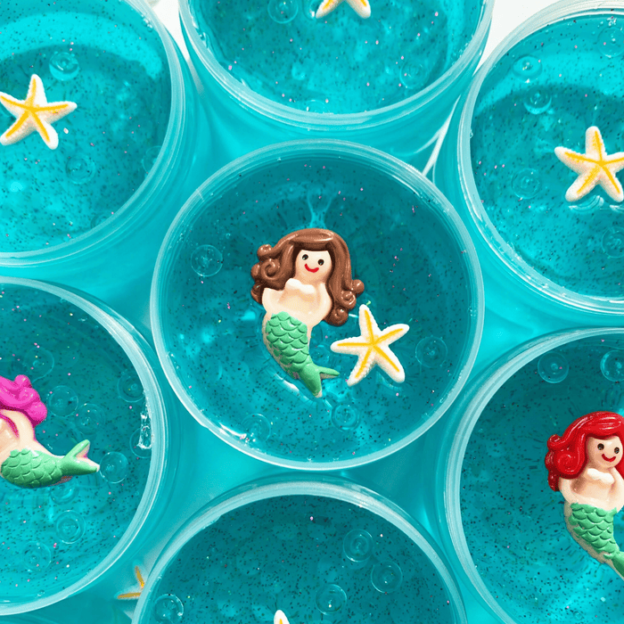 Several blue thick clear slimes in their containers. Three slimes have a white and yellow star charm as decoration. One slime has a mermaid and star charms as decorations.