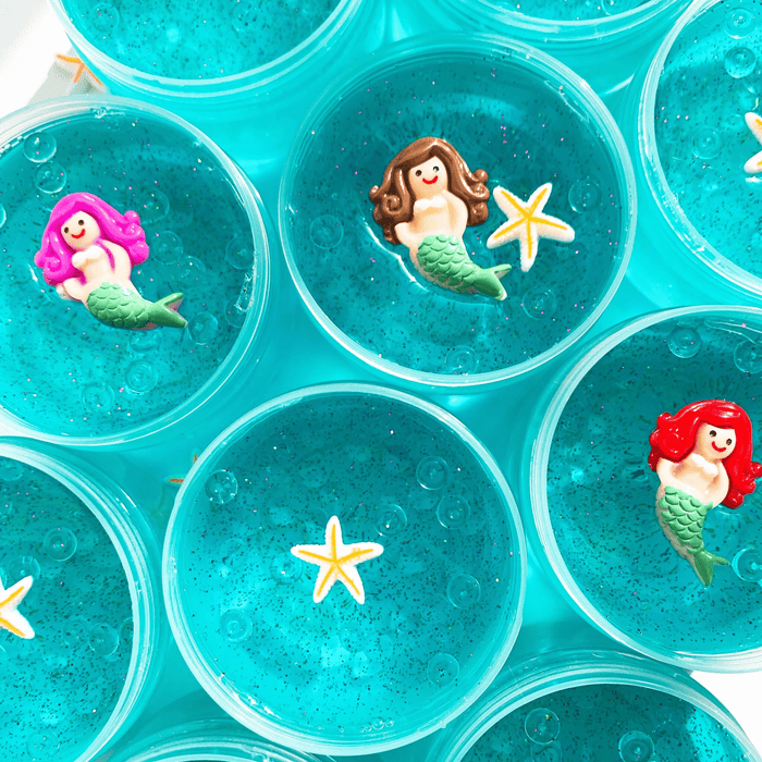 Many thick clear aqua colour slimes in their containers. One has a white and yellow star charm as decoration. Two slimes have mermaid charms and one has a mermaid and a star charm as decoration.