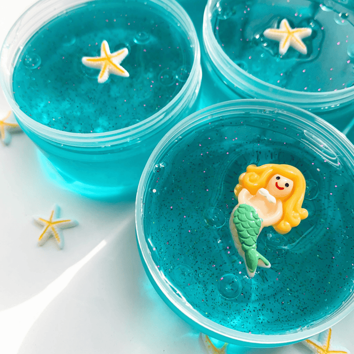 Close up to one blue thick clear slime in its container with a yellow-haired mermaid. In the back two blue thick clear slimes with a yellow and white star charm as decoration.