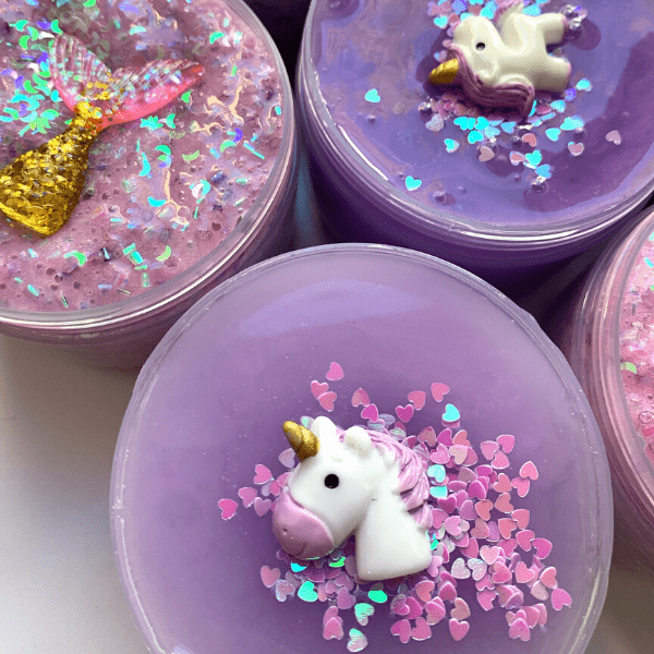 Close up to Lillac Lullabies slime with pink heart-shaped sprinkles and a white and purple unicorn charm as decoration.