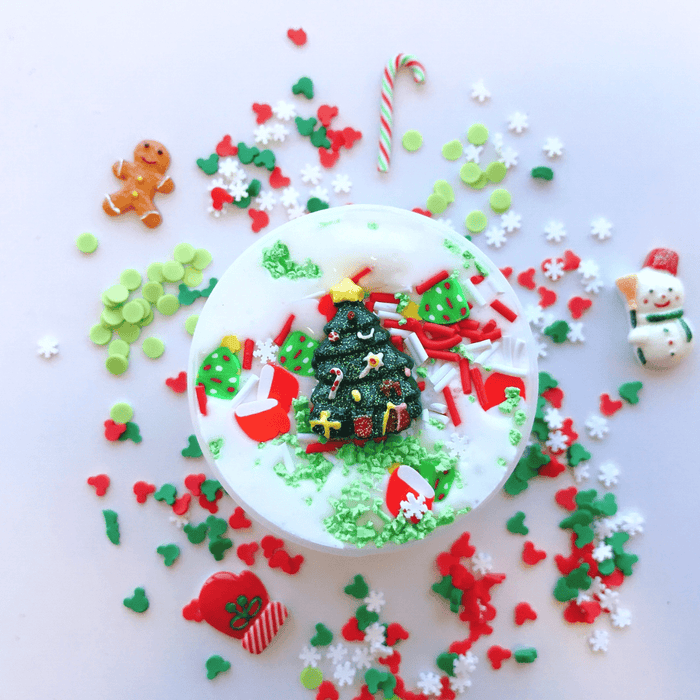 Christmas themed, white thick slime with Christmas tree charm as a decoration, white, red and green sprinkles and christmas tree and red winter mittens as decoration.