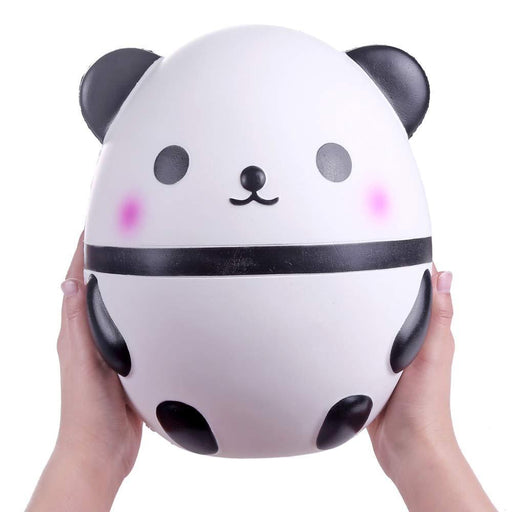 Two hands holding a round white and black panda squishy with pink cheeks