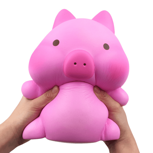 A hand holding a pink piggy squishy