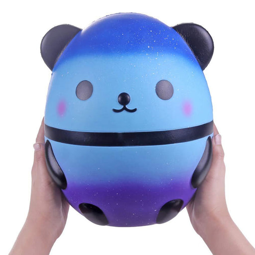 Two hands holding a gradient blue and purple panda squishy with white spots