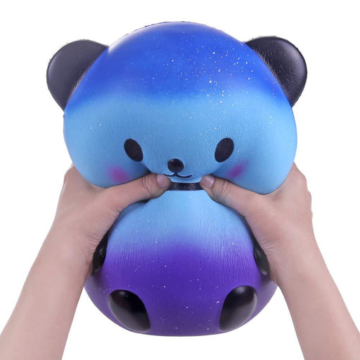 Two hands squishing a round blue and purple panda squishy