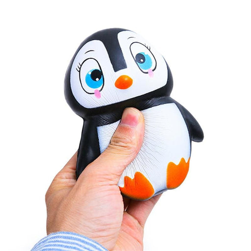 A hand squishing a black penguin squishy with a white belly, orange beak and feet, blue eyes and pink cheeks