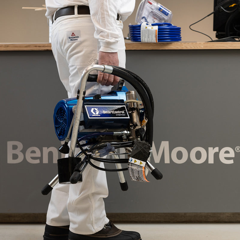 A man holding a Graco paint sprayer.