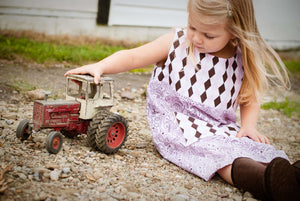 Girl Playing With a Tractor on a Family Farm