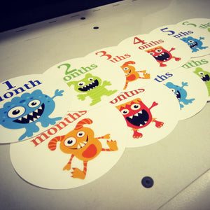 Monthly baby stickers. Cute monsters bodysuit infants month labels.