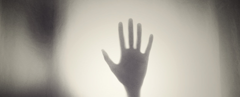 hand silhoutte behind glass foggy