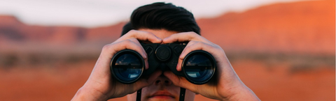 man looking at the camera through his binoculars