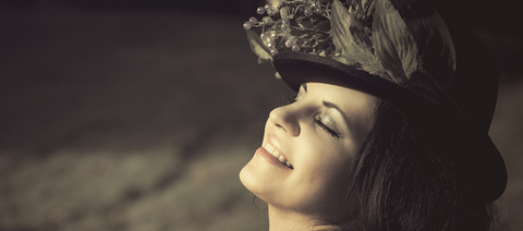 woman with hat closing her eyes feeling good