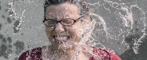 woman with reading glasses splashed with water