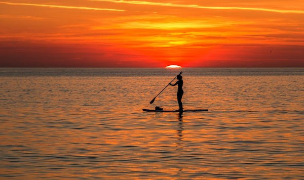 paddleboarding in sunset