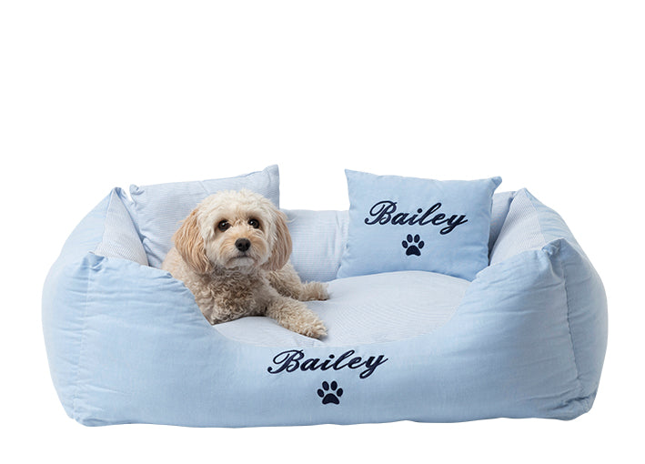 Stylish summer dog bed with pale blue exterior and blue and white striped interior, personalised with navy blue embroidery