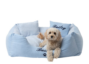Modern dog bed with a pale blue cotton material and navy blue embroidery of dog name