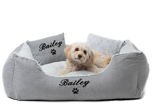 Modern dog bed with black embroidery of dog's name on a grey cotton and fluffy material
