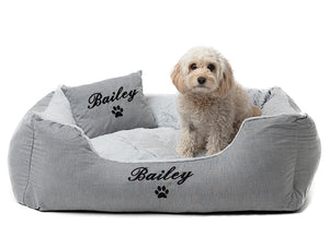 Luxury grey dog bed with two show pillows and customisation of dog's name in black embroidery.
