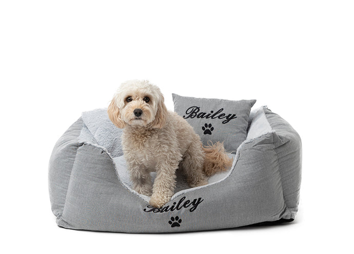 Grey cotton dog bed with a fluffy interior, personalised embroidery of dog name and signature paw in black