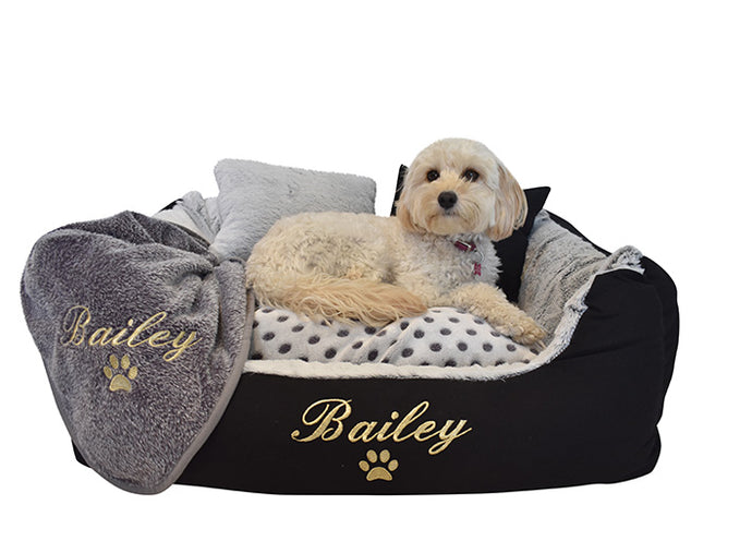 Personalised dog blanket with gold embroidery of dog name over Bailey's Beds dog bed