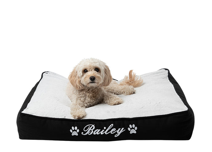 "Customisable dog mat, personalised dog bed, black cotton exterior and white fluffy material with white embroidery of dog name ""Bailey"" and two dog paws"