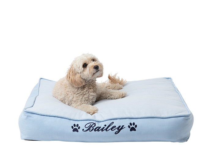 Small mat for dogs embroidered with dog name on the front of a pale blue cotton cover