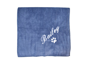 "Flatlay of blue personalised dog towel with name ""Bailey"" and signature paw embroidered in white"