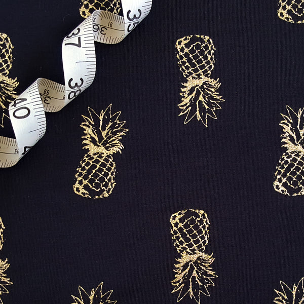 Gold glitter pineapples on navy jersey knit fabric