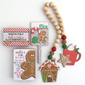 Gingerbread bread themed beaded garland with phrase blocks and Naughty/Nice plant stick.  Rae Dunn Christmas tiered tray decor.  Hot Cocoa tiered tray.  Christmas handmade decorations, Christmas wood decorations.