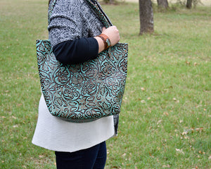 Dress up your outfit with a beautiful Tanned Cowhide/Stamped Leather Tote