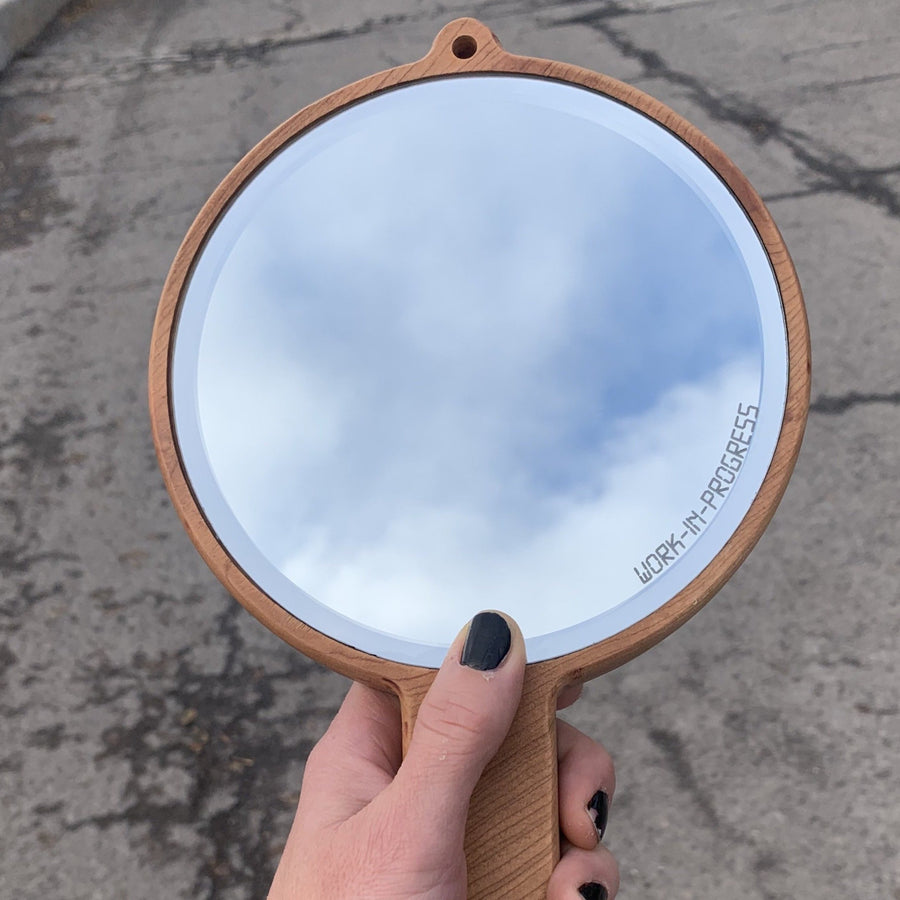 rounded cherry wood handheld mirror being held by a hand with the reflection of the sky and clouds in the mirror. laser etched on the side of the mirror are the words work in progress