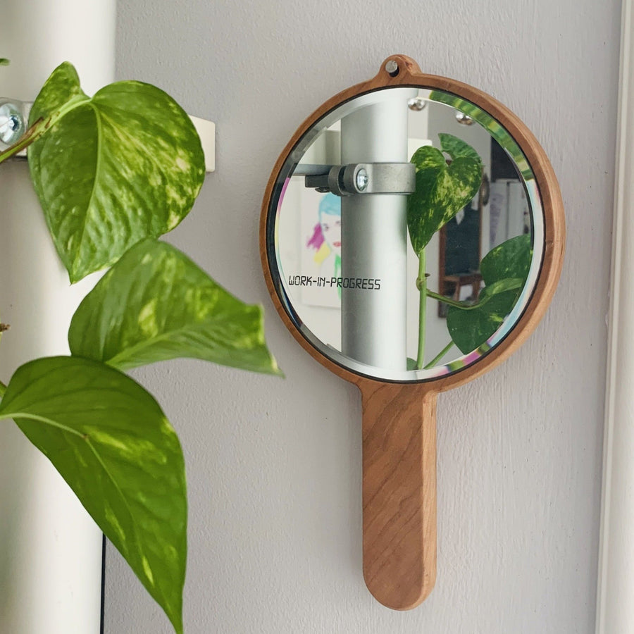 rounded wooden hand held mirror hanging on a wall with a plant beside it. laser engraved on the mirror are the words work in progress
