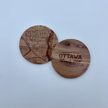laser etched wood coasters side by side. one of the coasters has a map etched on it, the other one has the words champion of the hood ottawa sandy hill.