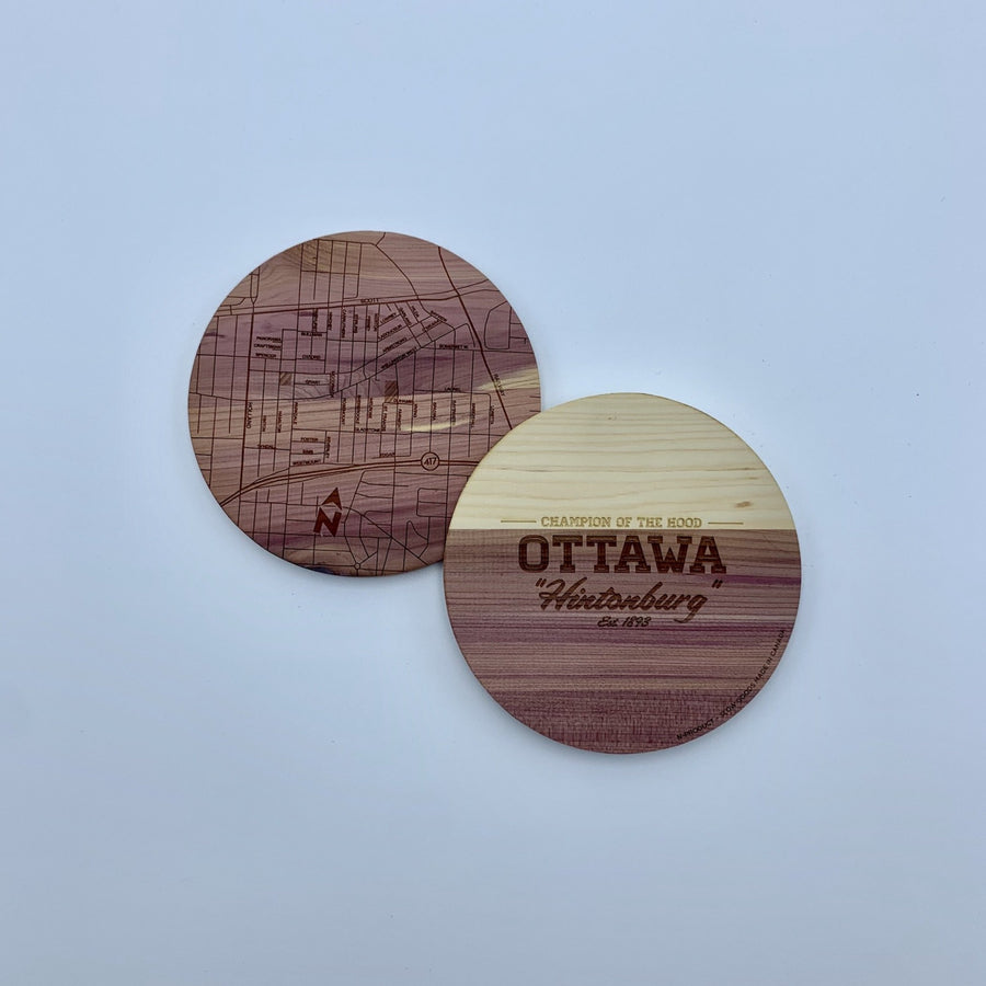 laser etched wood coasters side by side. one of the coasters has a map etched on it, the other one has the words champion of the hood ottawa hintonburg..