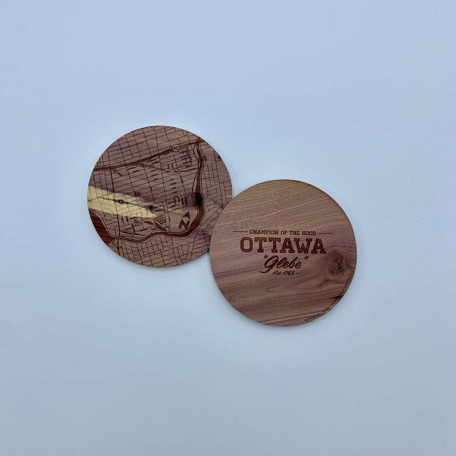 laser etched wood coasters side by side. one of the coasters has a map etched on it, the other one has the words champion of the hood ottawa glebe.