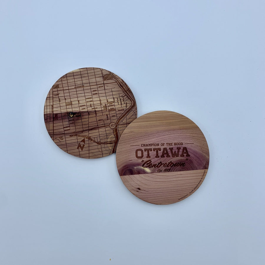 laser etched wood coasters side by side. one of the coasters has a map etched on it, the other one has the words champion of the hood ottawa centretown.