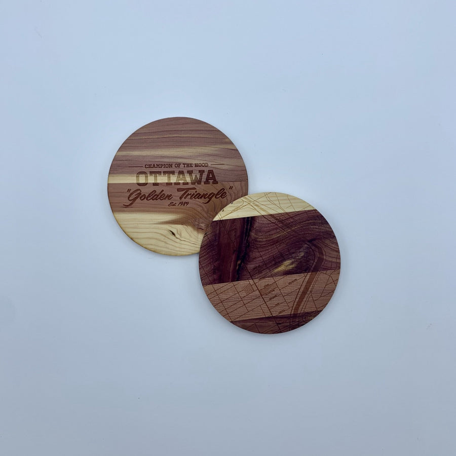 laser etched wood coasters side by side. one of the coasters has a map etched on it, the other one has the words champion of the hood ottawa golden triangle..