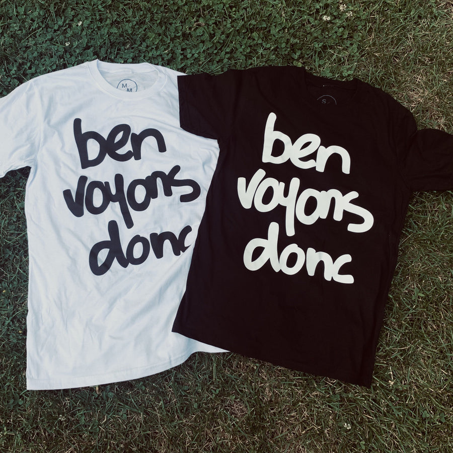 white ben voyons donc tee shirt with black lettering. black ben voyons donc tee shirt with whilte lettering. lying in the grass side by side